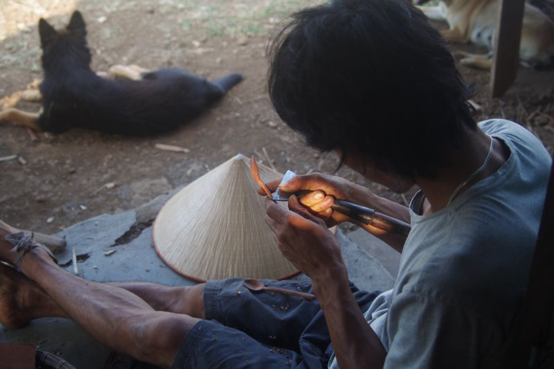 Huy is making wooden spoons