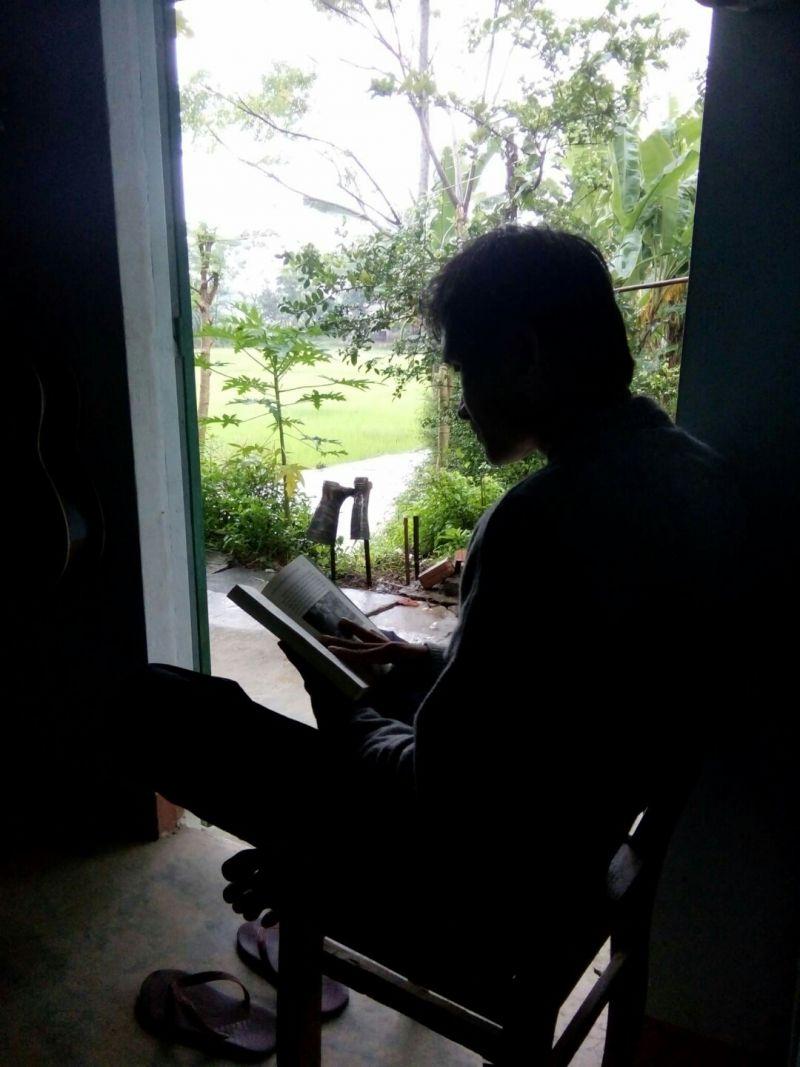 Nhat is at his reading corner, looking to the rice field
